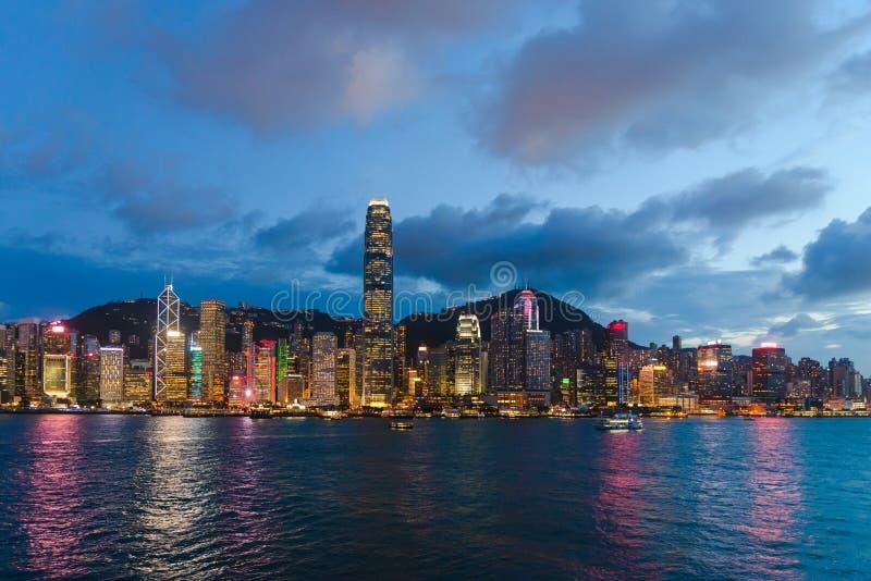 都市风景和地平线在维多利亚港口暮色时间的 普及的见解问题的日落时间的香港市 图库摄影