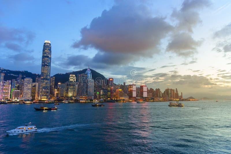 都市风景和地平线在维多利亚港口暮色时间的 普及的见解问题的日落时间的香港市 免版税图库摄影