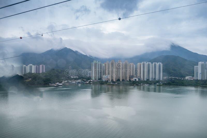 都市风景,下雨天,位于海边的大厦 有在大厦后的山 免版税库存图片