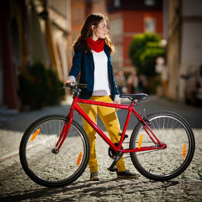 都市骑自行车-十几岁的女孩和自行车在城市 免版税图库摄影