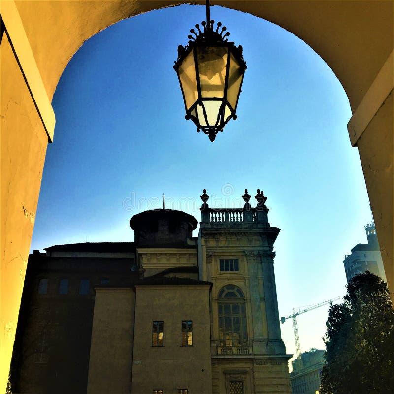 都灵市、曲拱、街灯和Madama宫殿 库存照片