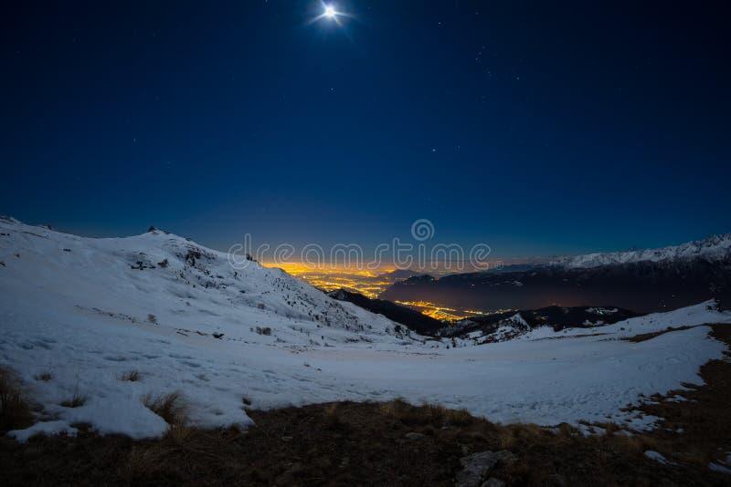 都灵市光,从积雪的阿尔卑斯的夜视图由月光 月亮和猎户星座星座,清楚的天空 意大利 免版税库存照片