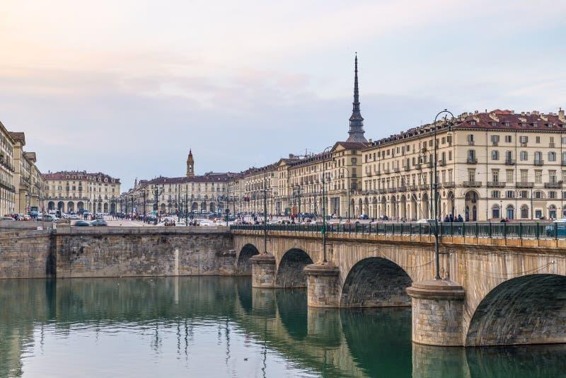 都灵街道生活、意大利,托里诺地平线与痣Antonelliana和桥梁在波河 人走的汽车通行,烟雾a 免版税库存图片