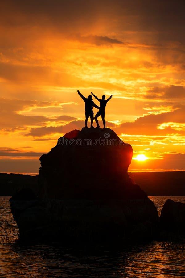 配合在海和山的友谊剪影 免版税库存照片
