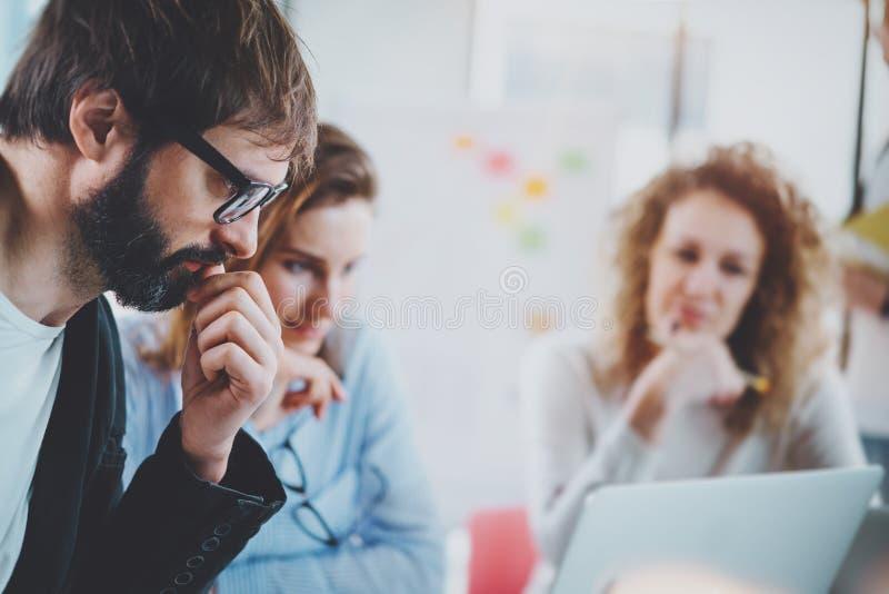 配合处理概念 年轻工友与新的起始的项目一起使用在晴朗的办公室 水平,被弄脏的背景 免版税库存图片