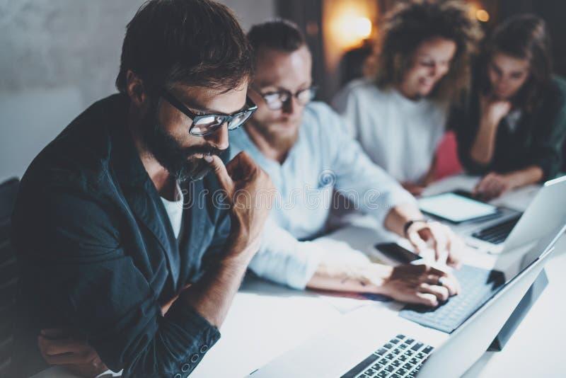 配合概念 做交谈的项目小组在会议室在夜办公室 使用膝上型计算机和小配件的人们 库存照片