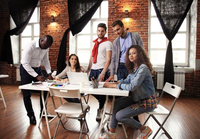 配合概念 年轻创造性的工友与新的起始的项目一起使用在现代办公室 人分析数据 免版税图库摄影