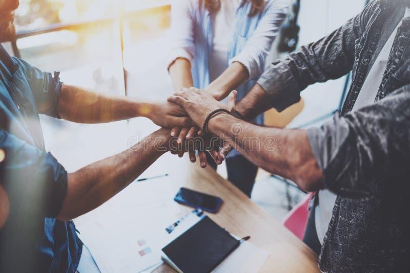 配合概念 在他们的会议期间,小组三个工友一起加入手 水平 被弄脏的背景 图库摄影