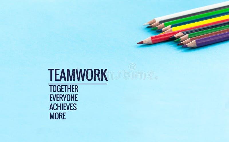 配合概念 小组在蓝色背景的颜色铅笔与词配合,一起,大家,达到和更多 免版税库存图片