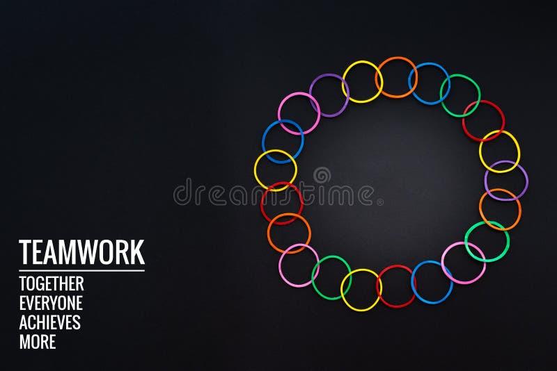 配合概念 小组在黑背景的五颜六色的橡皮筋儿与词配合,一起,大家,达到和更多 库存图片
