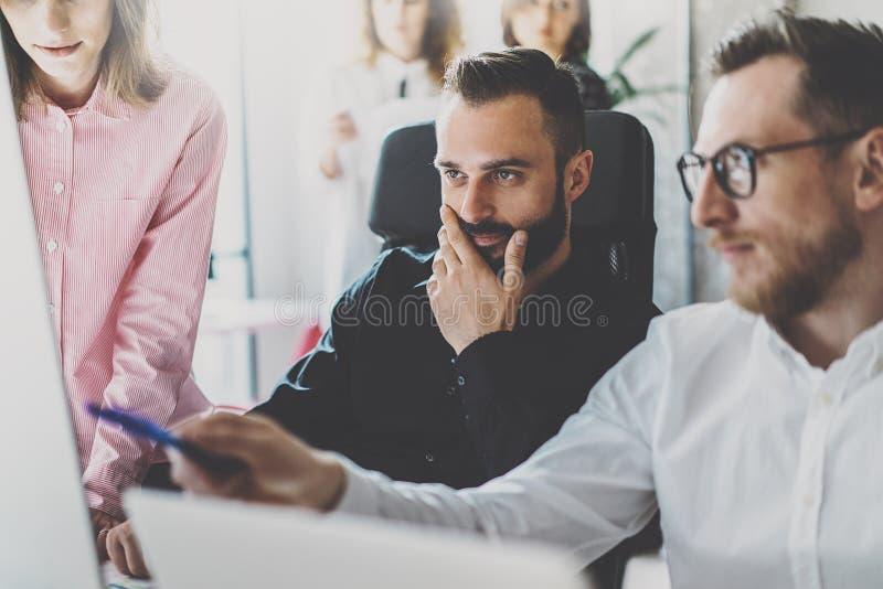 配合概念 谈论年轻的工友新的事务在现代办公室射出 小组三个人分析报告 图库摄影