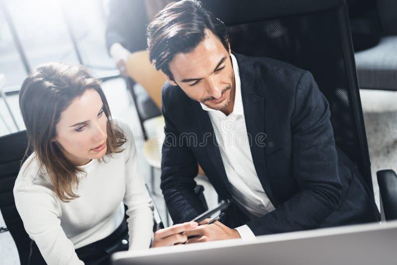 配合过程在lightful办公室 年轻商人与新的财务起动一起使用射出 被弄脏的背景 免版税库存照片