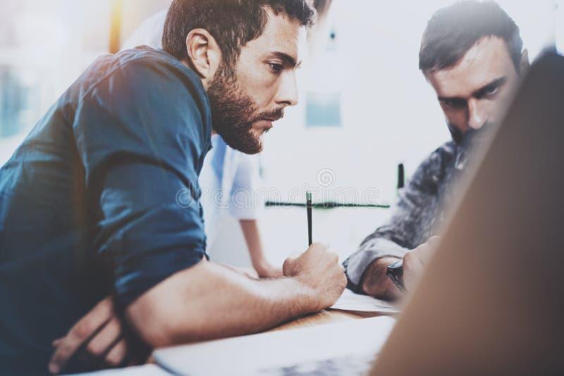 配合过程 现代coworking的演播室的小组年轻工友 做交谈与的青年人 库存图片