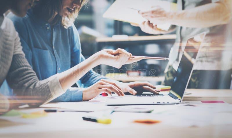 配合,群策群力概念 年轻创造性的经理在现代办公室合作与新的起始的项目一起使用 图库摄影