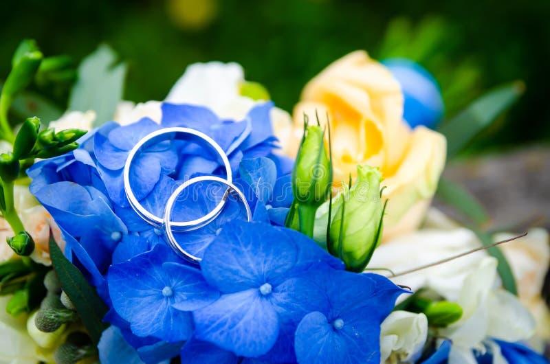 配对在新娘花束的背景的结婚戒指 免版税库存照片