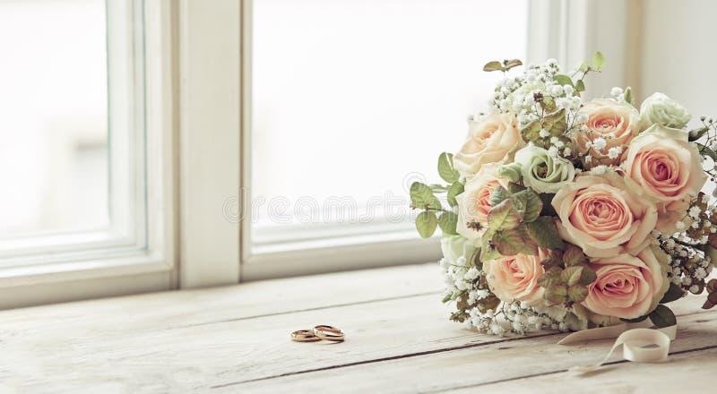 配对结婚戒指和新娘花束 免版税库存图片