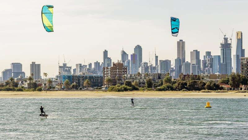 配对kitesurfers火车在菲利普港湾,与墨尔本地平线,澳大利亚在背景中 免版税图库摄影