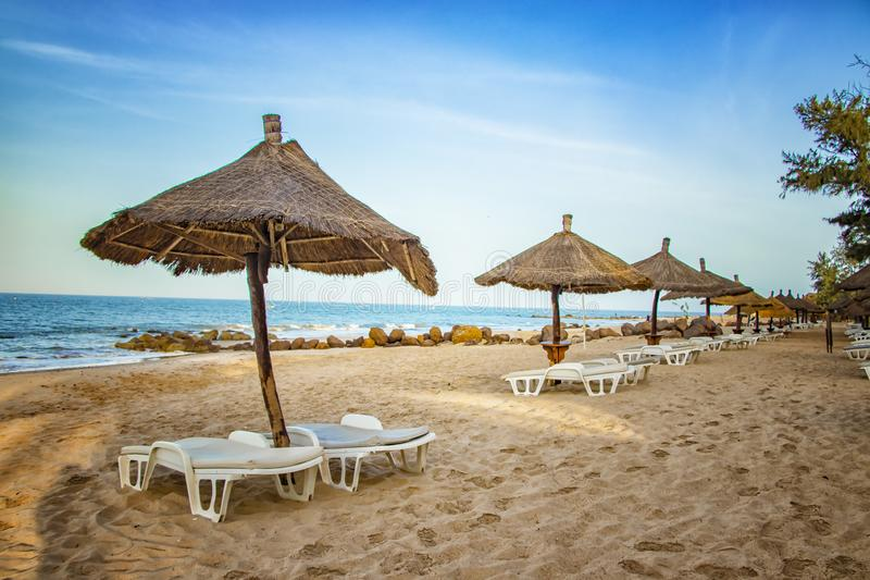 配对sunbed与在美丽的空的海滩的遮阳伞在清楚的海附近 这是一个热带天堂在非洲,塞内加尔 有蓝色的 免版税图库摄影