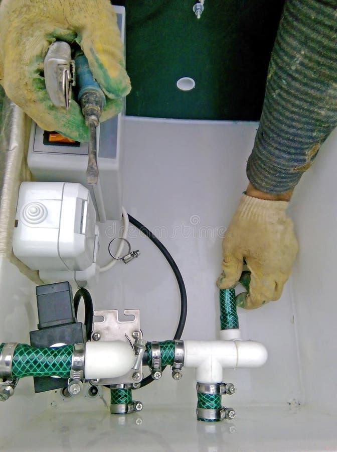 配管修理在废料治理坦克的建筑承包商塑料管子 库存照片