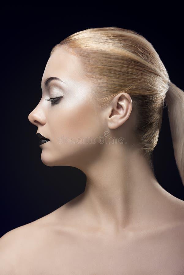 配置文件的白肤金发的女孩与黑暗的唇膏 免版税库存照片