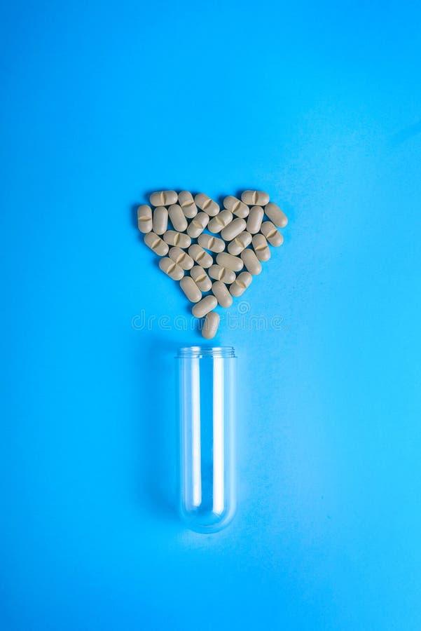 配药医学药片、片剂和胶囊心脏病的治疗的 心脏形状和瓶药片 图库摄影