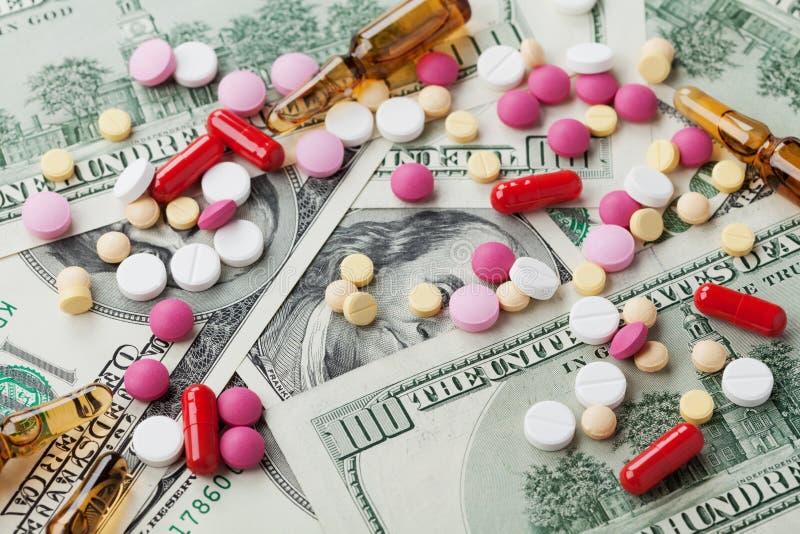 配药药物和医学药片堆在美元现金金钱、费用医药产品和治疗概念驱散了 免版税库存照片