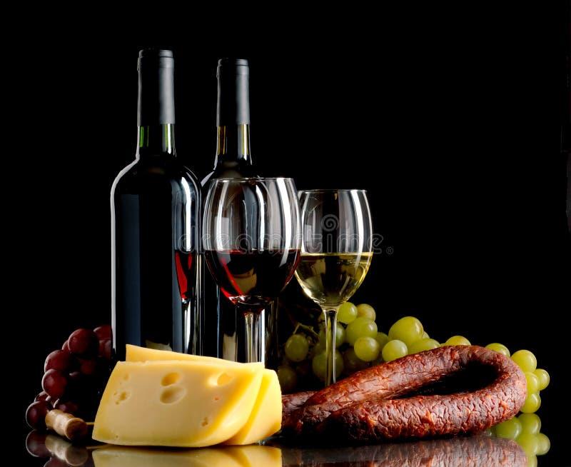 酒、葡萄、乳酪和香肠在黑背景 免版税库存照片