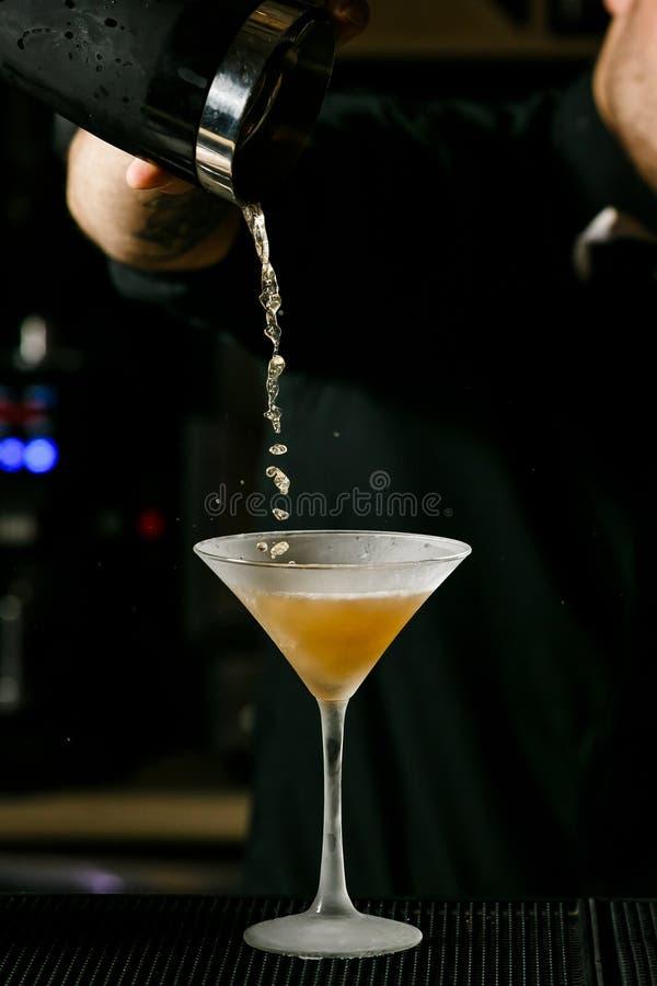 酒吧内部混合的酒精鸡尾酒的年轻英俊的男服务员 专业侍酒者在工作 库存照片
