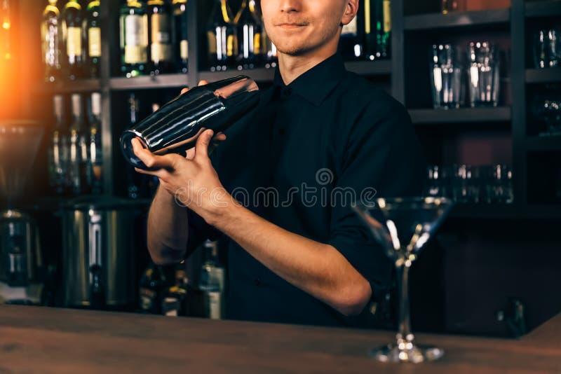 酒吧内部震动的和混合的酒精鸡尾酒的年轻男服务员 专业侍酒者画象在工作在夜总会 免版税库存图片