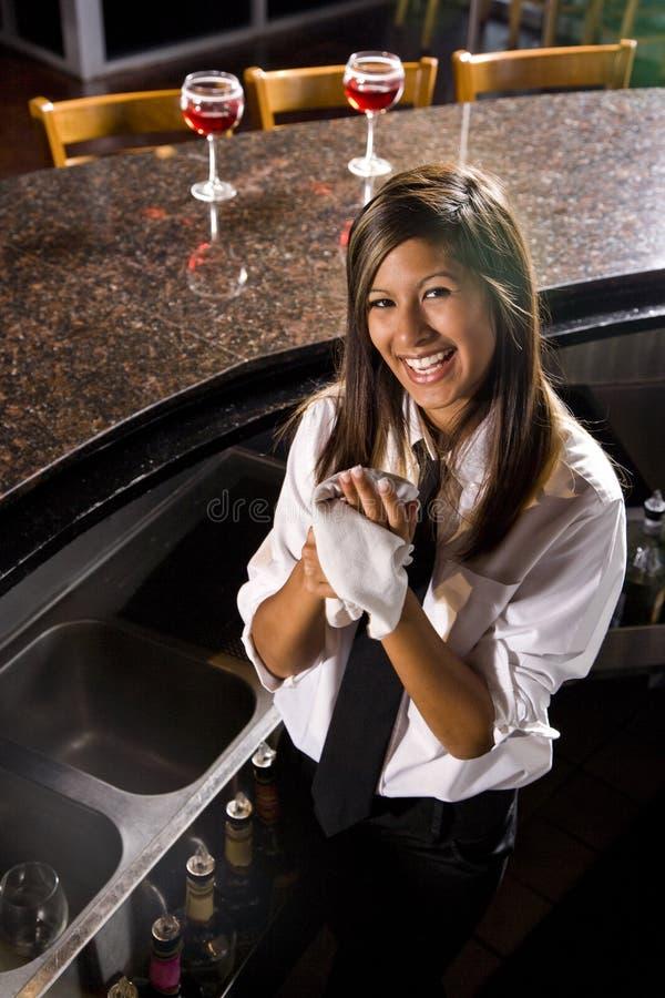 酒吧招待女性愉快的西班牙年轻人 库存照片