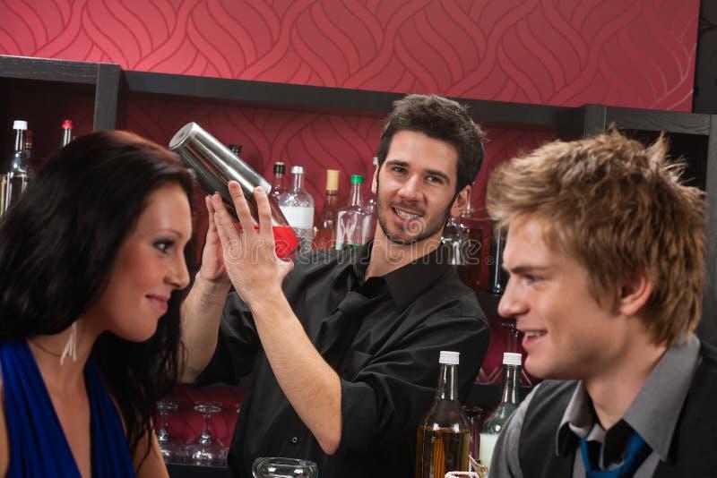 酒吧招待鸡尾酒有饮料的朋友震动 免版税图库摄影