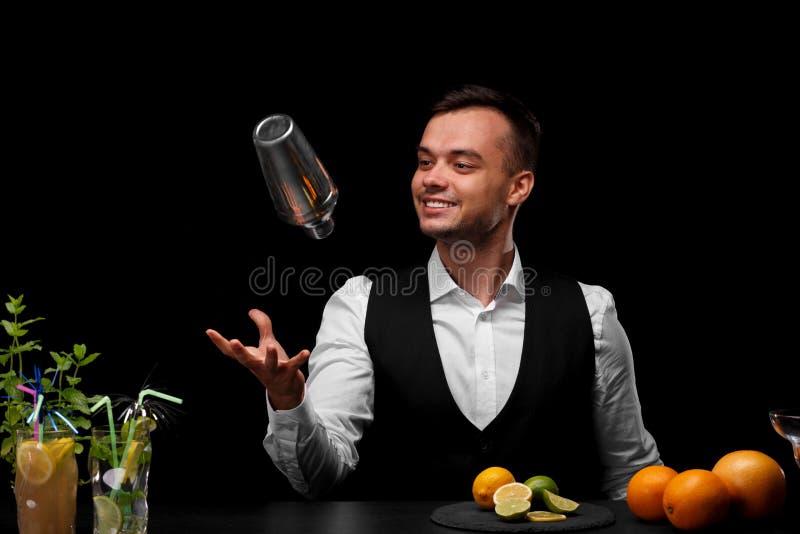 酒吧柜台的一位侍酒者扔一个振动器、石灰、柠檬、桔子和鸡尾酒在黑背景 库存照片