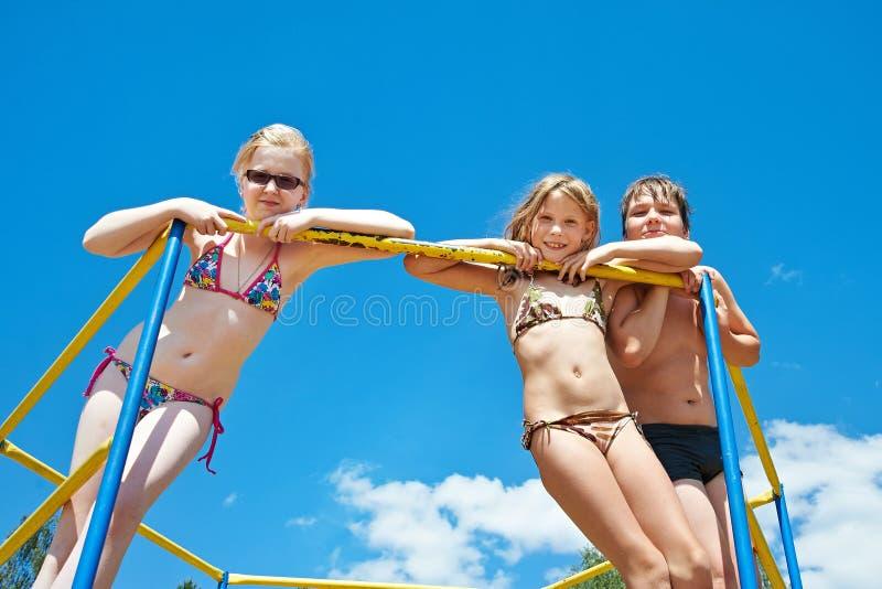 酒吧的三个快乐的孩子在操场 库存照片