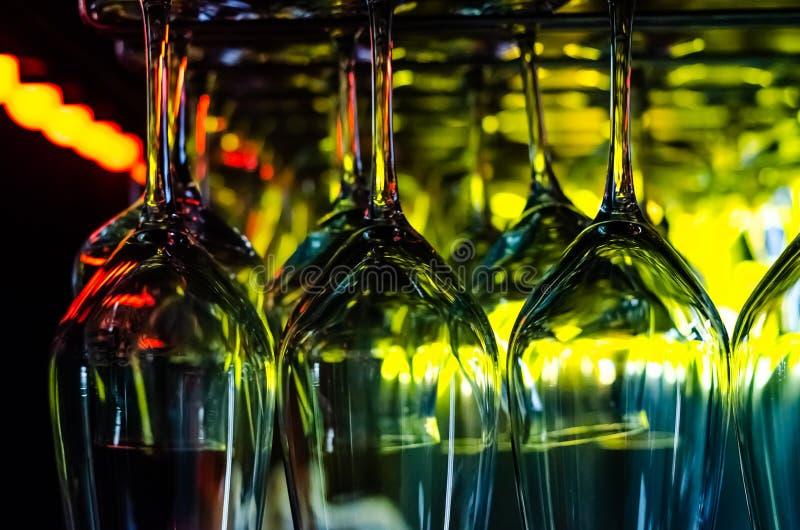 酒吧的五颜六色的光在酒吧柜台上的干净的空的玻璃被反射 客栈或酒吧内部在晚上 库存照片