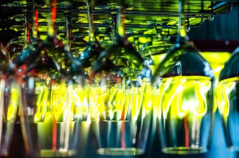 酒吧的五颜六色的光在酒吧柜台上的干净的空的玻璃被反射 客栈或酒吧内部在晚上 免版税库存照片