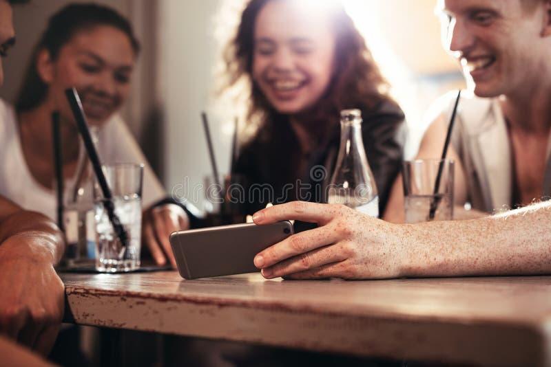 酒吧的朋友观看在手机的滑稽的录影 库存照片