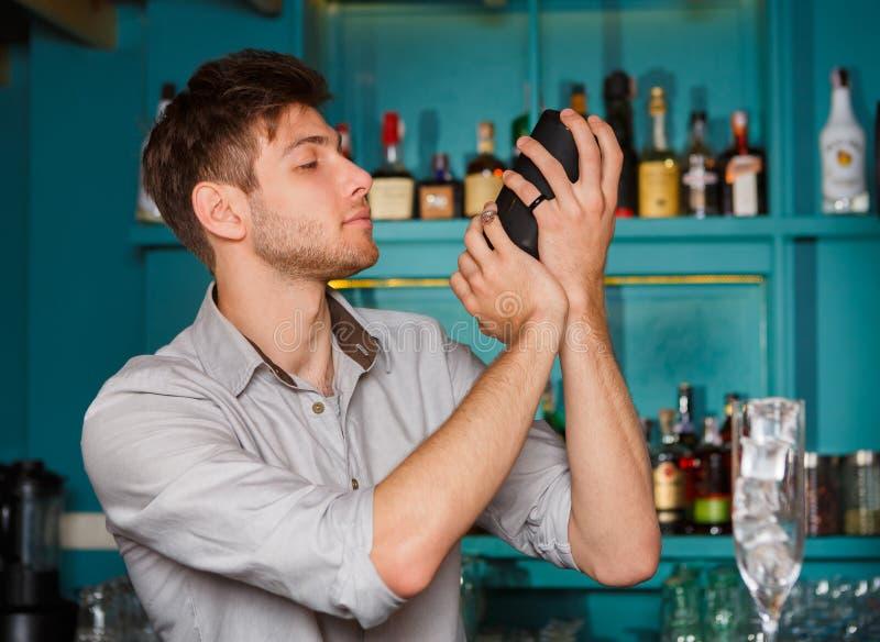 酒吧震动的和混合的酒精鸡尾酒的年轻英俊的男服务员 库存照片
