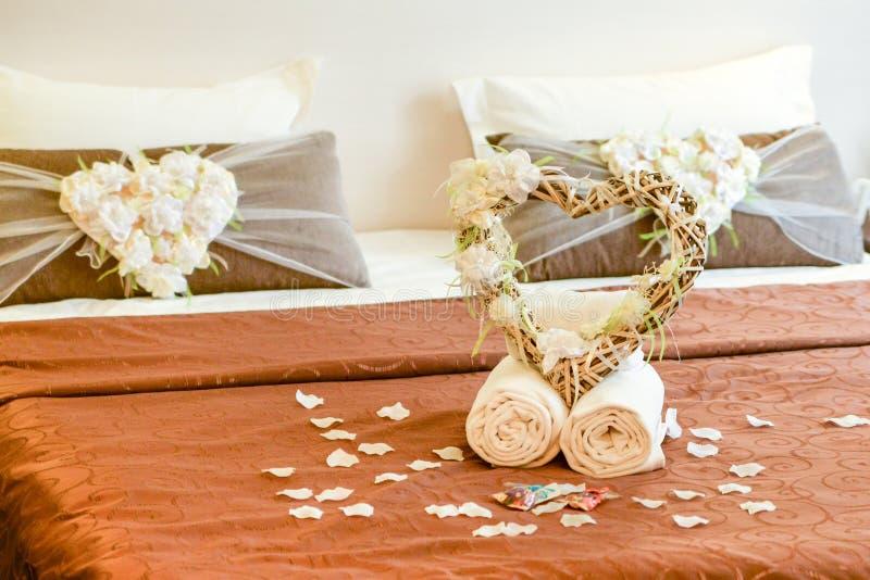酒店房间,蜜月、婚礼和爱概念-与心脏的两块毛巾在婚姻的床上冠上了与玫瑰花瓣 库存照片