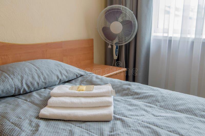 酒店房间 在床上是三块毛巾,肥皂,香波,阵雨胶凝体 库存照片