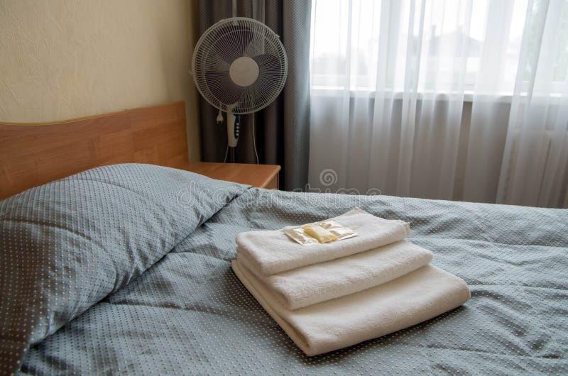 酒店房间 在床上是三块毛巾,肥皂,香波,阵雨胶凝体 免版税库存图片