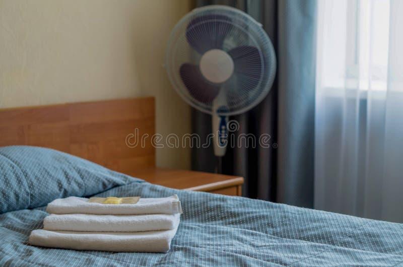 酒店房间 在床上是三块毛巾,肥皂,香波,阵雨胶凝体 免版税库存照片