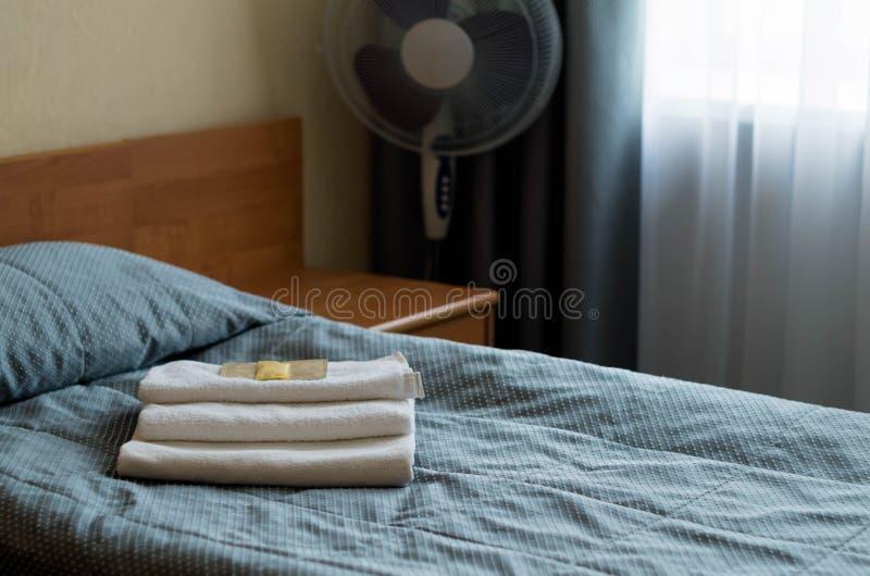 酒店房间 在床上是三块毛巾,肥皂,香波,阵雨胶凝体 库存图片