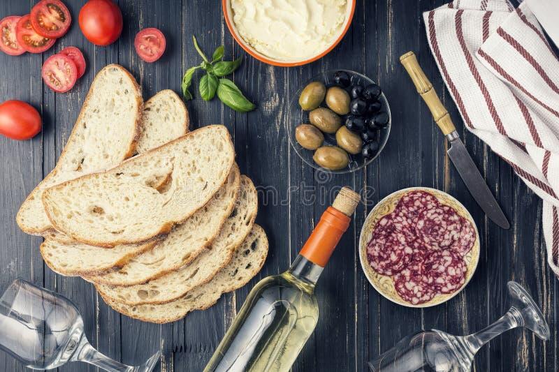 酒快餐集合 意大利快餐,整个蒜味咸腊肠, ciabatta, 酒 橄榄 传统地中海桌 木背景,名列前茅vi 免版税库存照片