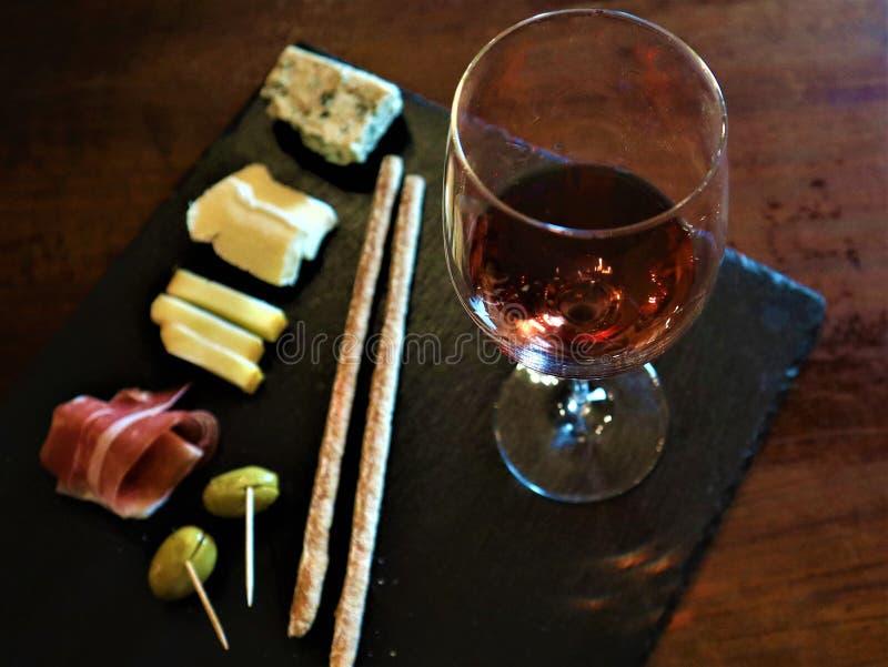 酒快餐集合 杯红酒、绿色地中海橄榄、熏火腿、蒜味咸腊肠和年迈的乳酪在土气木背景 库存照片