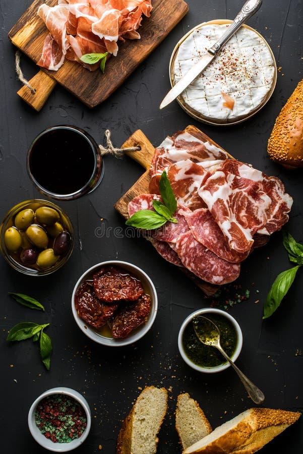 酒快餐集合 红色,肉选择,地中海橄榄,各式各样的蕃茄,长方形宝石切片,软制乳酪玻璃  图库摄影
