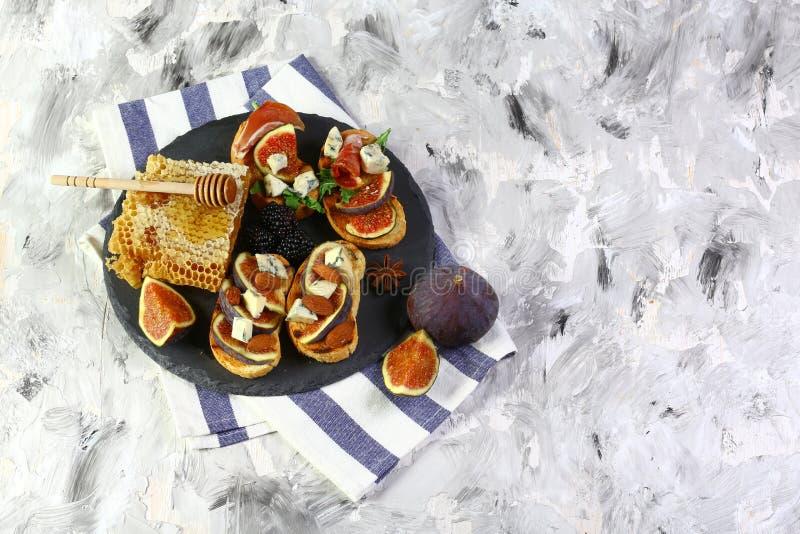 酒或快餐的-熏火腿,无花果,面包,在页岩板的乳酪可口开胃菜 在灰色背景,顶视图 免版税库存图片