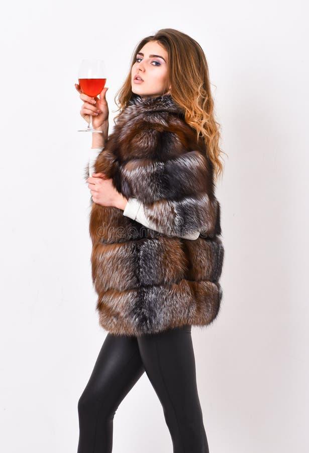 酒文化概念 妇女饮料酒 女孩时尚构成穿戴毛皮大衣举行玻璃酒精 精华休闲 原因 库存图片