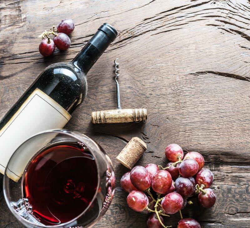 酒杯、酒瓶和葡萄在木背景 酒ta 库存照片