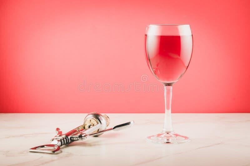 酒杯和拔塞螺旋在桃红色背景/酒杯和拔塞螺旋在桃红色背景 r 免版税图库摄影