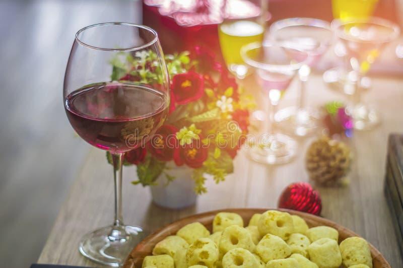 酒杯和鸡尾酒和精神和苹果和金鱼瓶子,投入了一张木桌在圣诞晚会 库存照片